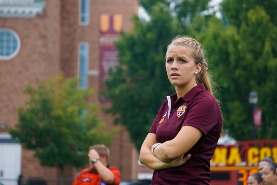 Student assistant coach Emily Hansen stands on the sideline as she watches the women's soccer team play against Cansius.
