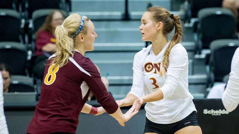 Archibald (right) congratulates teammate junior Jessica Paolucci after a play.