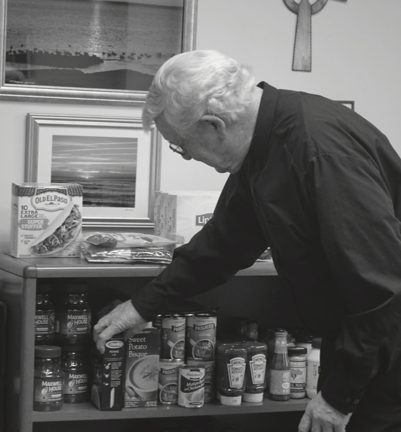 Brother Devlin sets out some of the products donated to the food pantry in his office.
